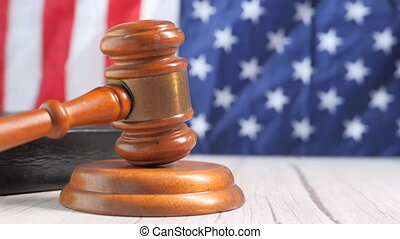 Closeup of gavel and book against american flag .
