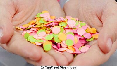 Closeup of girl blowing off confetti - Girl blows confetti...