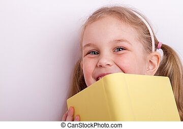 Closeup of girl face behind book cover