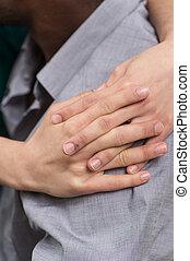 closeup of girl hands hugging boyfriend shoulder. side view of black man wearing shirt