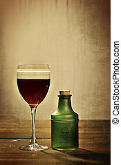 glass red wine with poison bottle - closeup of glass red ...