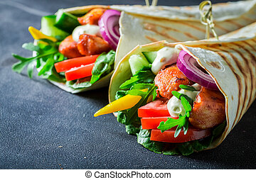 Closeup of grilled tortilla with chicken, tomatoes and lettuce