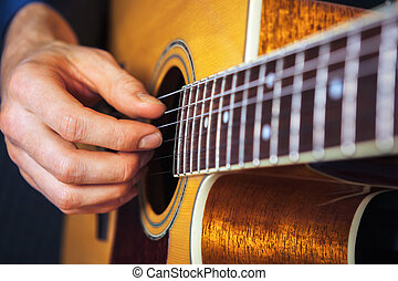Closeup of guitarist hand practicing with chords.