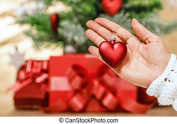Closeup of hand holding a toy in the shape of a heart on the bac
