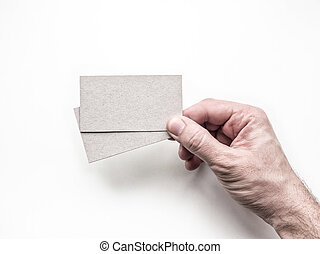 Closeup of hand holding two business cards on the white wall, Mockup