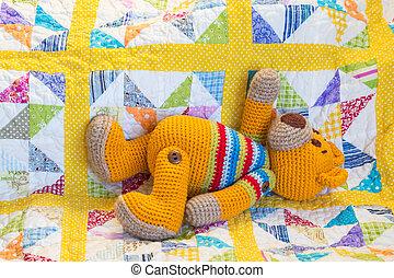hand made crochet teddy bear lying on quilt cover