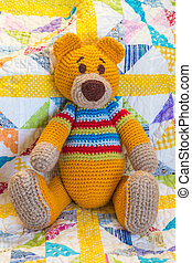 hand made crochet teddy bear sitting on quilt cover