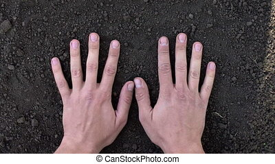 Closeup of hand of man making handprint in black ground