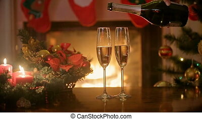 Closeup of hand pouring champagne in glasses on table at fireplace