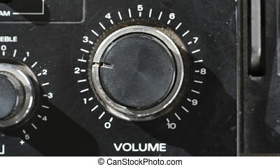 closeup of hand turning a volume control on an old hifi