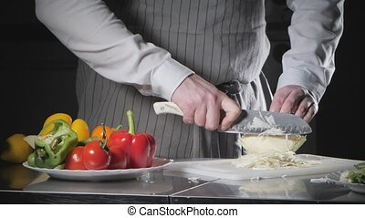 Closeup of hand with knife cutting fresh vegetable. Young chef cutting cabbage on a white cutting board closeup. Cooking in a restaurant kitchen