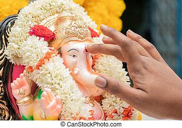 Closeup of hands applying Tilak or Kumkum to Lord Ganesha during Indian religious ganesha or vinayaka Chaturthi festival ceremony