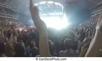 """Closeup of hands clapping in air. Silhouettes of many people enjoying concert"""