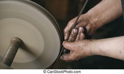 Closeup of hands grinding metal knife at grindstone machine...