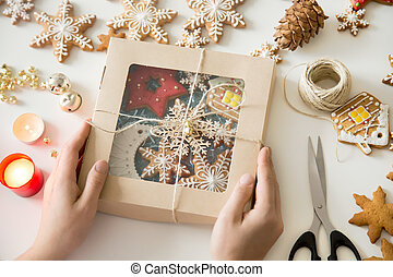 Closeup of hands holding a festive box with Christmas cookies