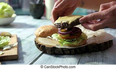 Closeup of hands preparing cheeseburger. Bottle pouring...