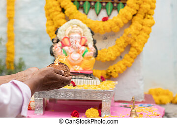 Closeup of Hands worshiping lord ganesh by offering aarti during vinayaka Chaturthi festival pooja or puja celebration at home in India.