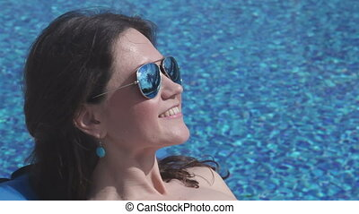 """Closeup of happy female face in sunglasses, woman suntanning"""