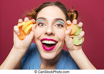 Closeup of happy funny young woman with marmalade candies