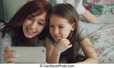 Closeup of Happy mother and little girl taking selfie photo...