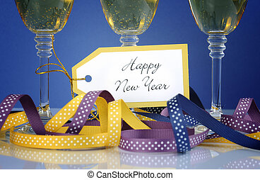 Closeup of Happy New Year greeting tag with three champagne glasses and party ribbons and decorations.