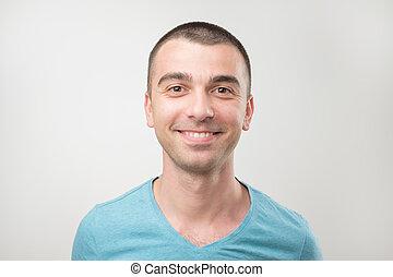 Closeup of happy smiling guy in blue shirt looking at camera