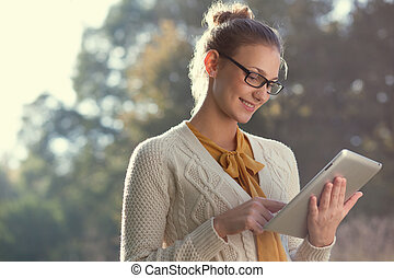 closeup of happy woman in glasses using tablet pc in the...