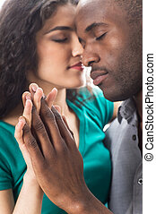 Closeup of happy young woman with boyfriend spending time together. Closeup portrait of african young couple isolated on white background.