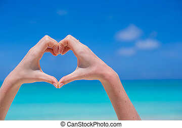 Closeup of heart made by hands background turquoise water