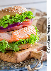 Closeup of homemade burger with big fish and vegetables