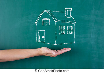 house drawn on black board in front of woman's hand -...