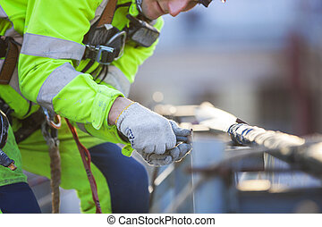 Closeup of industrial climber working on roof