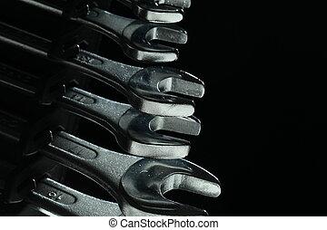 Closeup of iron spanners set over dark light