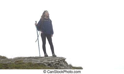 Closeup of joyful mountaineer young woman surrounded by mist standing on the mountain peak looking at the distant landscape