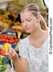 Closeup of lady holding a yellow tomato