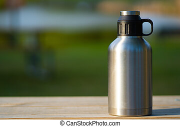Closeup of large thermos on a wooden table outside on a green blurred summer background