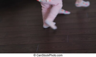 Legs of little child girls running around the room at home