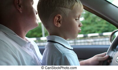 Closeup of little boy sitting on the hands of his father at the wheel in the car