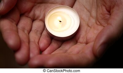 Candle in hands. Close up. Background of candle lighting in...