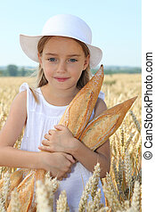 Closeup of little girl holding bread in wheat field