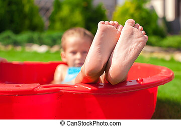 Closeup of little kid's legs in small red pool