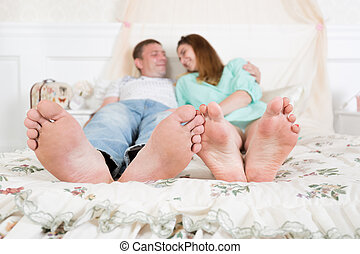 Closeup of loving couple feet lying in bed