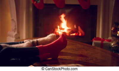 Closeup of male and female feet in woolen socks warming at fireplace