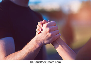 Closeup of male and female handshake outdoors
