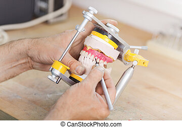 Closeup of male dental technician's hands working with...