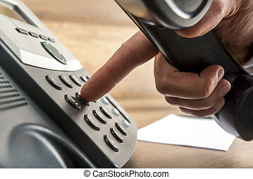Closeup of male hand dialing a telephone number on black...