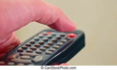 Closeup of male hand pushing remote control buttons -...