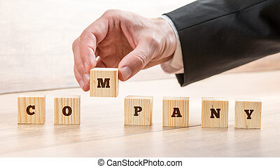 Closeup of male hand putting together word COMPANY on seven wooden cubes. Conceptual of building a competent business team