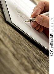 Closeup of male hand signing business contract, subscription form or insurance papers with fountain pen