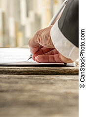 Closeup of male hand signing contract or application form on a rustic wooden desk